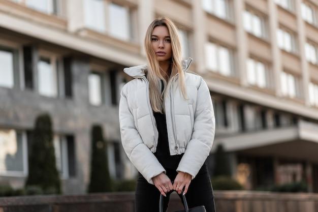 Model van een jonge vrouw in een wit jasje en een trendy leren tas staat in de stad