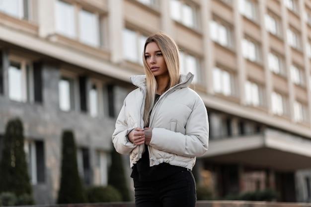 Model van een jonge vrouw in een wit jasje en een trendy leren tas staat in de stad Premium Foto