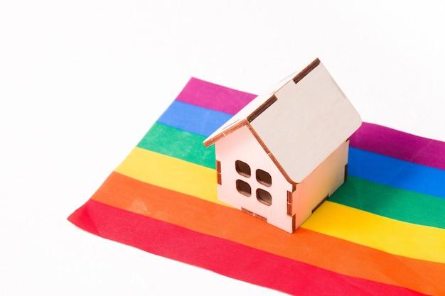 Model van een klein houten huis staat op de vlag van regenboogkleuren