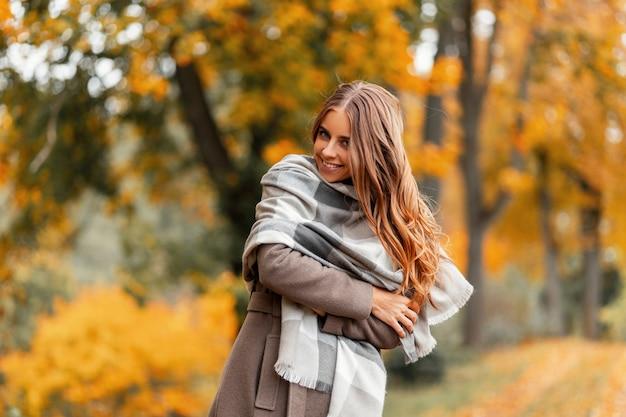 Model van een positieve jonge vrouw in een jas in een gebreide sjaal poseren in een park op een achtergrond van bomen met oranjegele loof. gelukkig meisje met een schattige glimlach buiten op het platteland in het bos