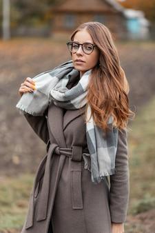 Model van een stijlvolle jonge hipster vrouw in een modieuze jas in trendy bril in een gebreide vintage sjaal wandelingen op het platteland. aantrekkelijk schattig meisje. elegante herfst dameskleding.