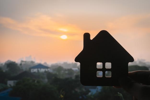 Model van het huis in de hand van een verzekeringsagent of een verkoper.