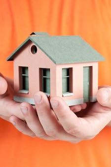 Model van het kleine huis in menselijke handen.