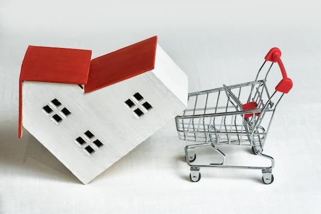 Model van huis en mand op wit. een huis kopen. vastgoed en hypotheek concept.