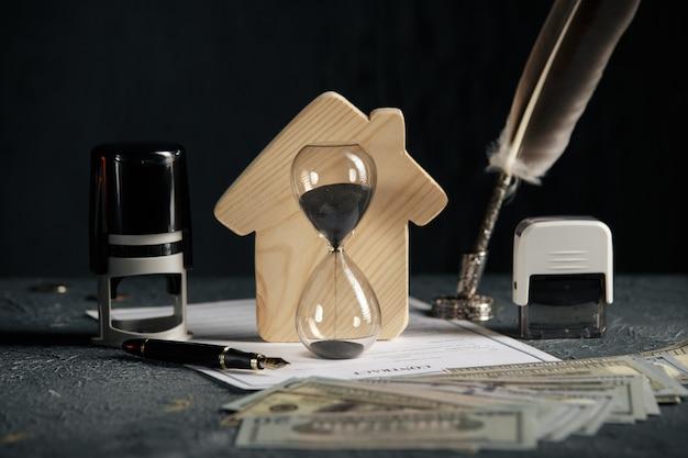 Model van huis, geld en zandloper. concept hypotheek of huur