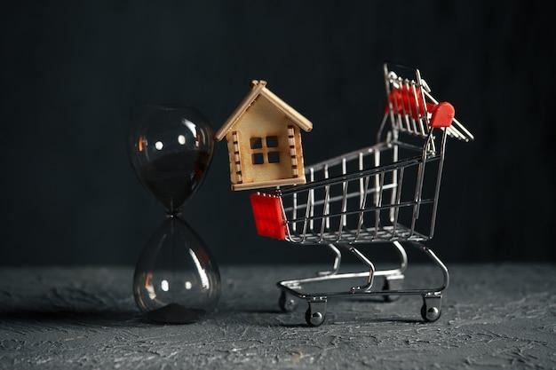 Model van huis, karretje en zandloper. een eigendomsconcept opslaan en kopen