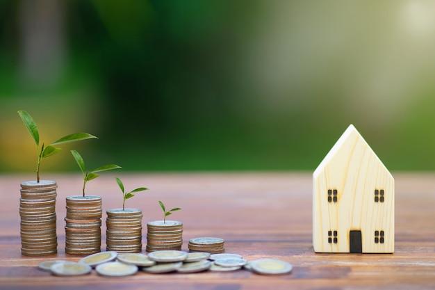 Model van huis met de stapel van geldmuntstukken