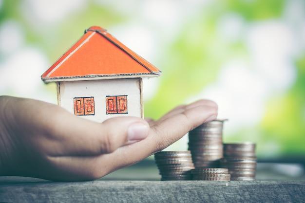 Model van huis met munten op houten tafel op onscherpe achtergrond