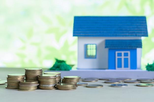 Model van huis met munten op houten tafel