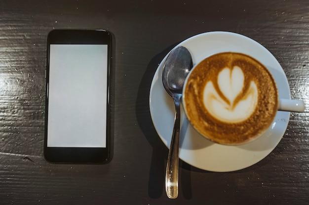 Model van mobiele telefoon bij een koffiekopje