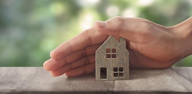 Model van vrijstaande miniatuur huis mock-up in de hand. onroerend goed investeringsconcept