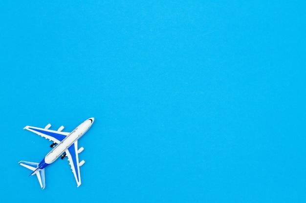 Model vliegtuig op blauwe hemel kleur achtergrond. plat ontwerp voor reisconcept