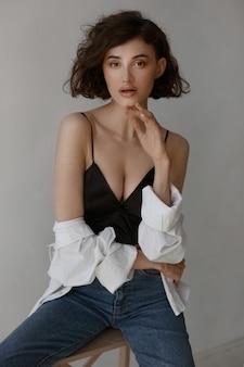 Model vrouw met trendy make-up en kapsel, gekleed in een verleidelijke outfit