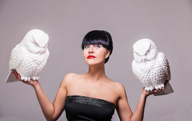 Model vrouw met twee decoratieve witte uil bij de hand