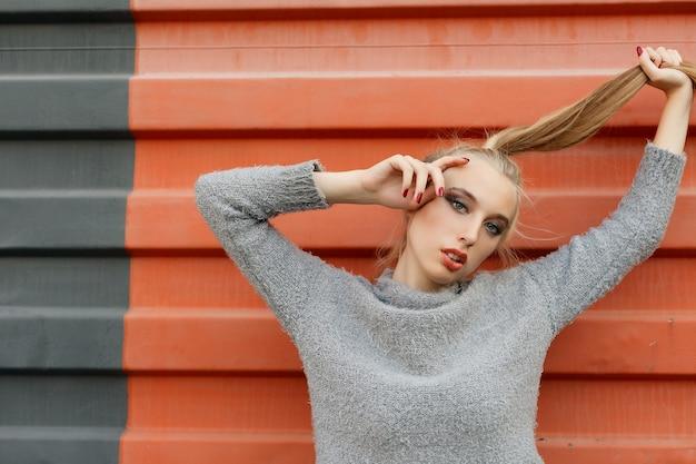Model wijst naar boven in de studio en kijkt naar de camera. geïsoleerde oranje achtergrond. glimlachende vrouw in trui poseren met gekruiste armen en kijken naar de camera over gele achtergrond