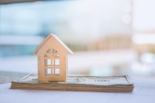 Model wit huis op dollarbankbiljet. verzekering en vastgoedbeleggingen onroerend goed concept.