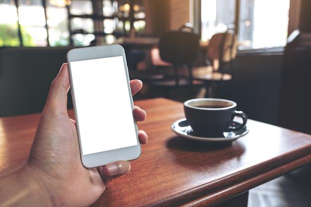Modelbeeld die van hand witte mobiele telefoon met het lege desktopscherm met koffiekop houden op houten lijst in koffie