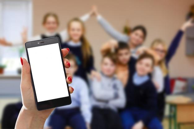 Modelbeeld die van hand witte mobiele telefoon met het lege witte scherm houden