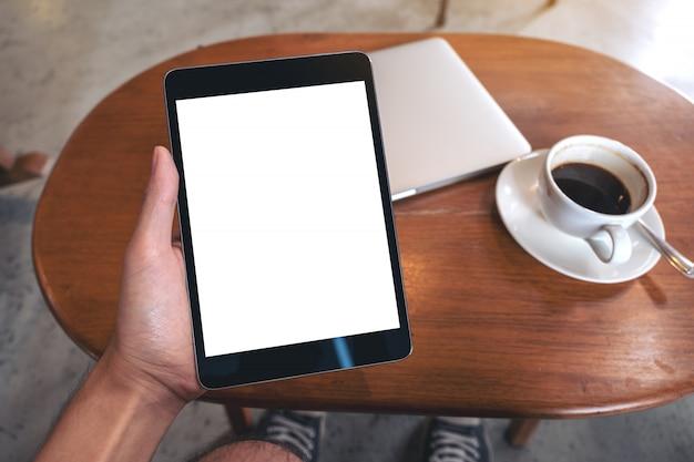 Modelbeeld die van hand zwarte tabletpc met het lege witte scherm van de desktop met laptop en koffiekop op houten lijst houden