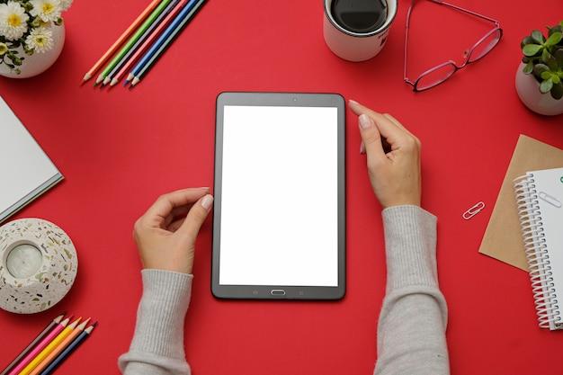 Modelbeeld die van handen tabletpc op rood bureau houden.