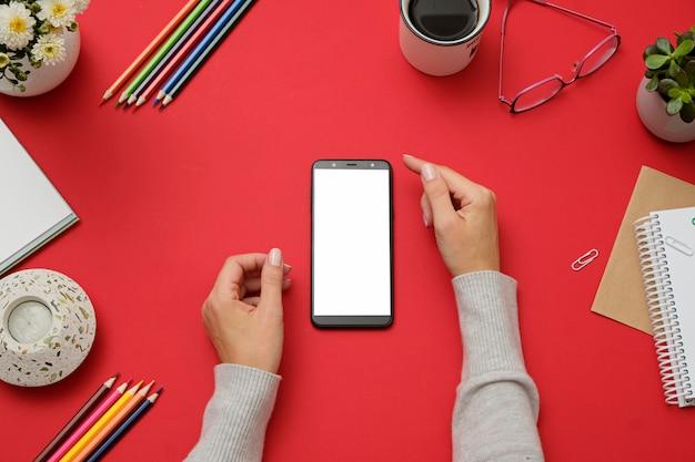 Modelbeeld die van handen witte mobiele telefoon op rood bureau houden.