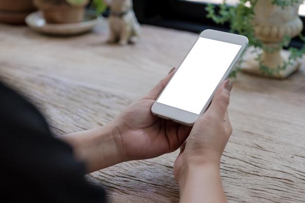 Modelbeeld van de handen die van de vrouw mobiele telefoon met het lege witte scherm op houten lijst in uitstekend koffie houden