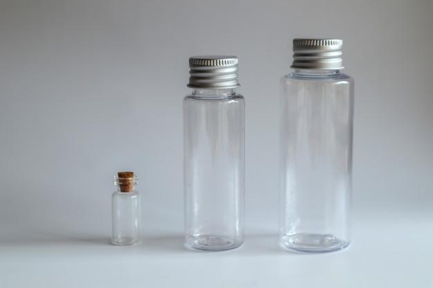 Modelbeeld van duidelijke glasfles met metaaldeksel op wit
