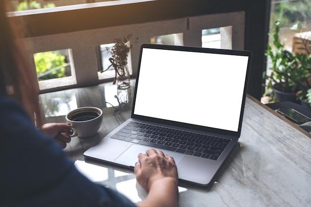 Modelbeeld van een vrouw die en op laptop met het lege scherm gebruikt typt terwijl het drinken van koffie in modern koffie