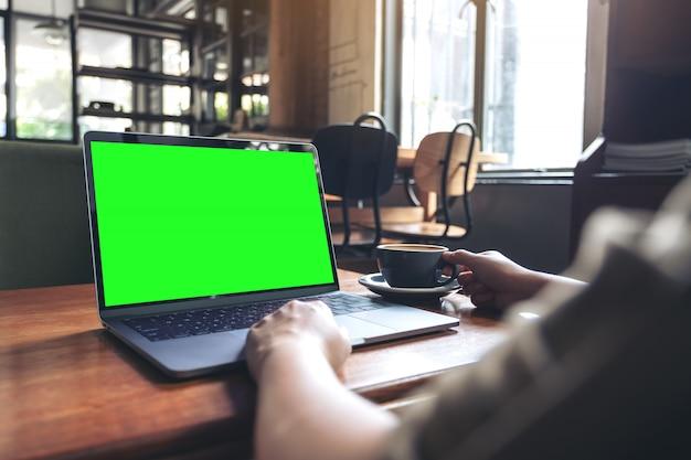 Modelbeeld van een vrouw die laptop met het lege desktopscherm met behulp van terwijl het drinken van hete koffie op houten lijst in koffie