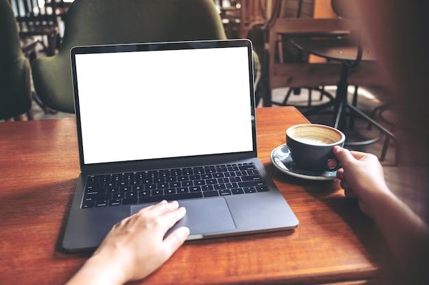 Modelbeeld van een vrouw die laptop met het lege witte desktopscherm met behulp van terwijl het drinken van hete koffie op houten lijst in koffie