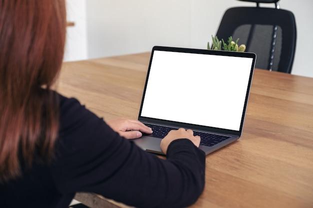 Modelbeeld van een vrouw die op laptop met het lege witte bureaubladscherm op houten lijst in bureau gebruikt en typt