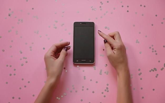 Modelbeeld van handen die witte mobiele telefoon met modern roze bureau houden