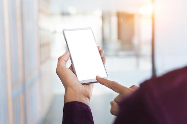 Modelbeeld van man handen die witte mobiele telefoon met lege het schermtechnologie houden.