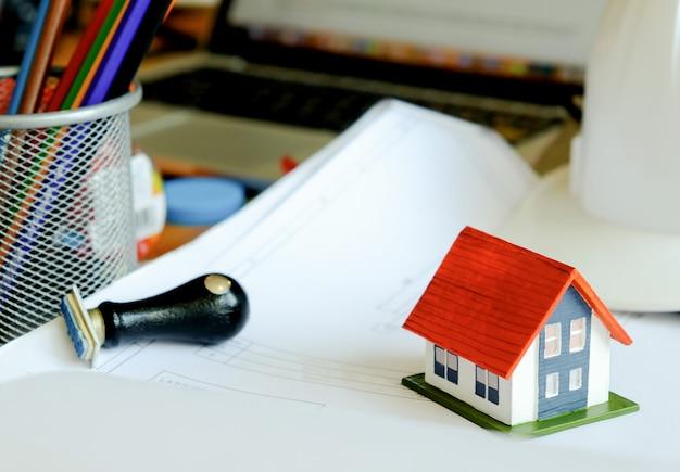 Modelhuis en rubberzegel op het huisplan op de lijst. voor huishandelzaken.