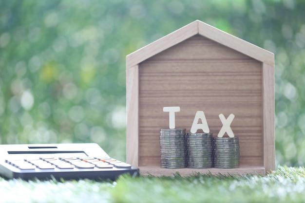 Modelhuis met stapel muntgeld en belastingwoord op groene achtergrond