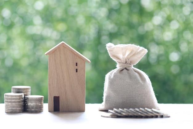 Modelhuis met stapel muntstukkengeld op natuurlijke groene achtergrond