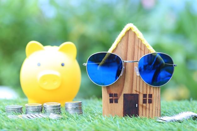 Modelhuis met zonnebril en stapel muntstukkengeld op natuurlijk groen