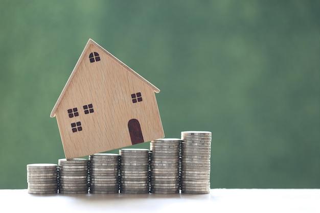 Modelhuis op stapel muntstukkengeld op natuurlijke groene achtergrond, investeringen en bedrijfsconcept