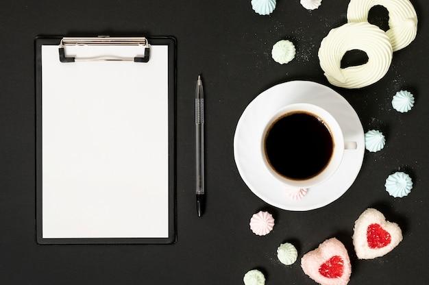 Modelklembord met kop koffie en schuimgebakjekoekjes