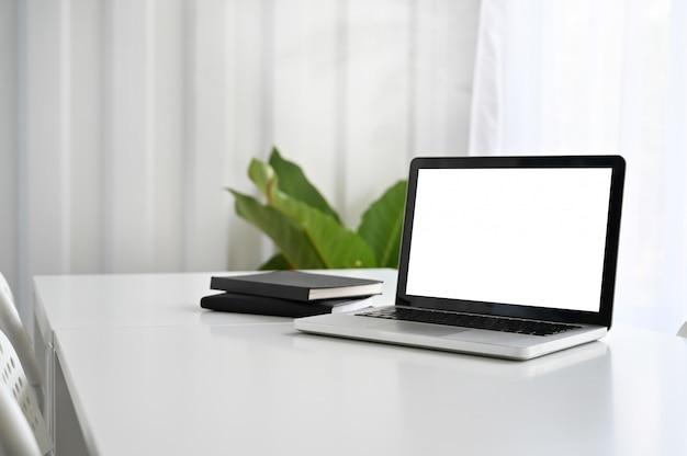 Modellaptop computer en notitieboekjedocument op werkende lijst.