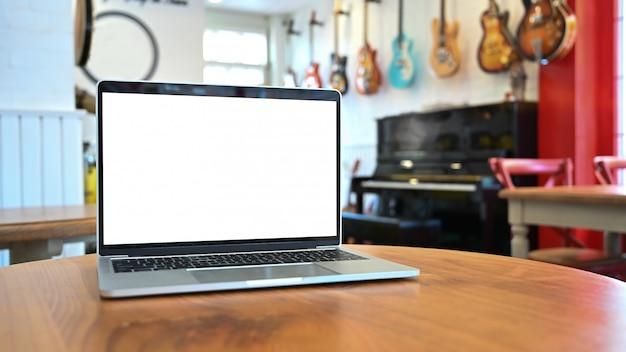 Modellaptop computer op houten lijst bij muziekhuis.