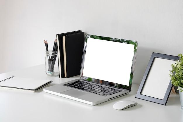 Modellaptop op werkruimte met fotokader, kruik potlood, muis op bureaulijst.