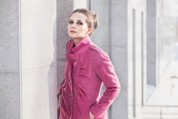 Modelleer een mooie vrouw in een modieuze jas aan de oppervlakte van het stedelijke landschap in de winter
