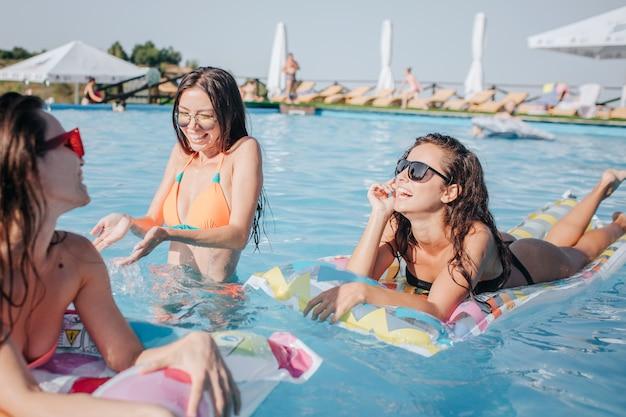 Modellen in bikini zwemmen op drijvers en staan in het water in het zwembad. vrouw in midden opspattend water met handen. andere twee modellen worden bruin en genieten. ze lachen.