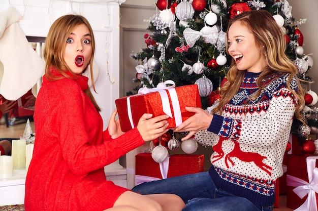 Modellen in warme winter truien zitten in de buurt van versierde kerstboom op oudejaarsavond.