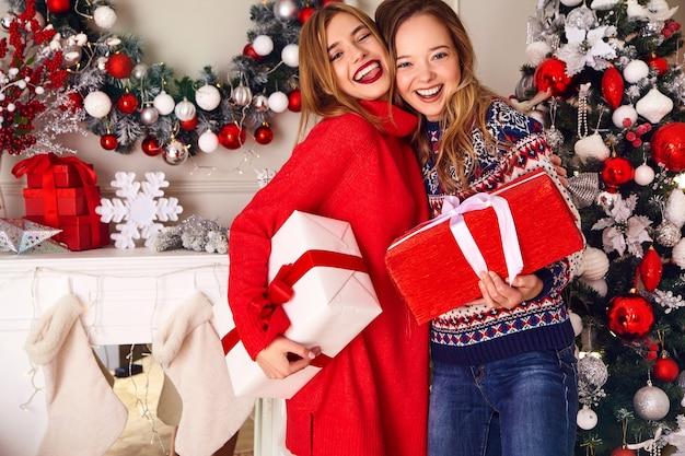 Modellen in warme winter truien zitten in de buurt van versierde kerstboom op oudejaarsavond. Gratis Foto