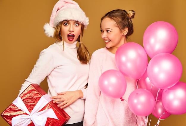 Modellen met grote geschenkdoos en roze ballonnen op kerstmis