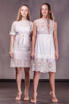 Modellen mooie vrouwelijke vriendinnen in zachte jurken met lang haar communiceren liefdevol met elkaar