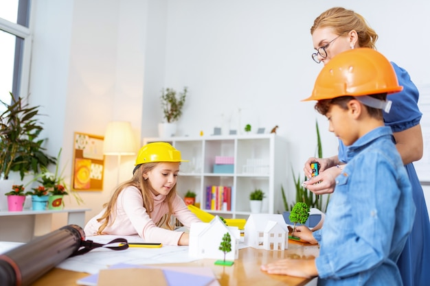 Modellen van bomen. jongen en meisje die modellen van bomen zetten en op tafel bouwen terwijl ze huismodellering bestuderen