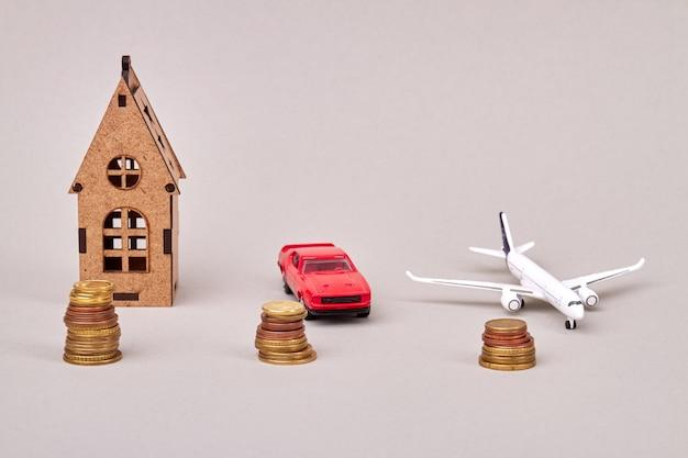 Modellen van huisauto en vliegtuig met geïsoleerde stapels muntstukken